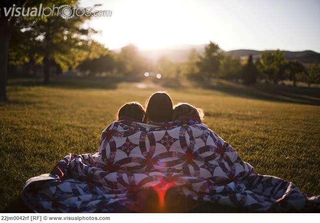 3 girls wrapped in blanket at sunset